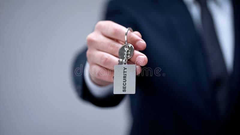 Palabra de la seguridad en llavero en la mano del hombre de negocios, sistema de seguridad casero, servicio del guardia fotografía de archivo libre de regalías