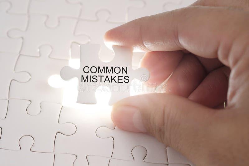 Palabra de los ERRORES COMUNES en rompecabezas El sostenerse de las manos del hombre de negocios fotos de archivo libres de regalías