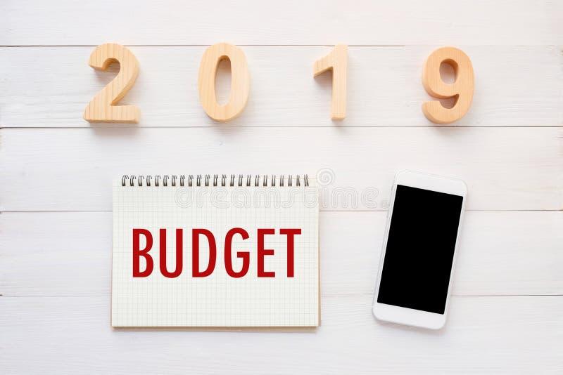 palabra de 2019 presupuestos en fondo del papel del cuaderno y el teléfono elegante en el fondo de madera blanco, concepto financ fotografía de archivo