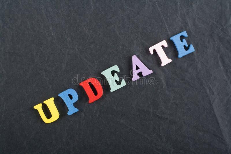 Palabra de UPDEATE en el fondo negro compuesto de letras de madera del ABC del bloque colorido del alfabeto, espacio del tablero  fotos de archivo libres de regalías
