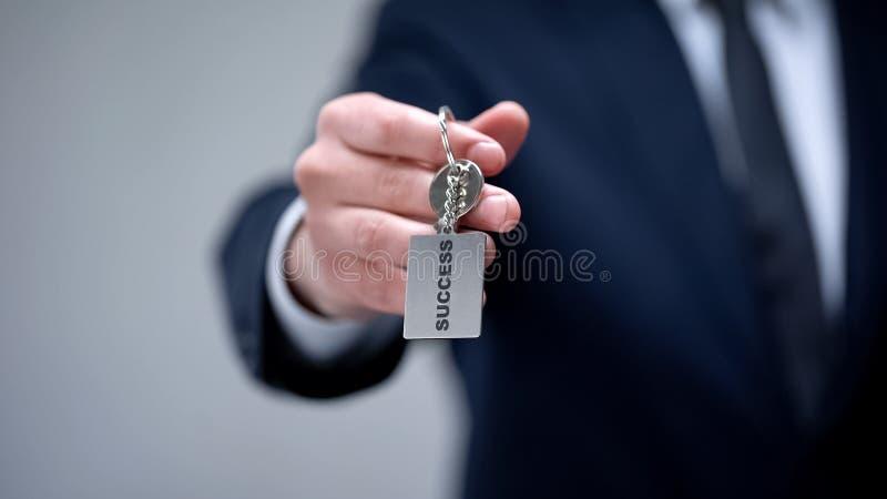 Palabra del éxito en llavero en la mano del hombre de negocios, cursos personales del desarrollo foto de archivo libre de regalías