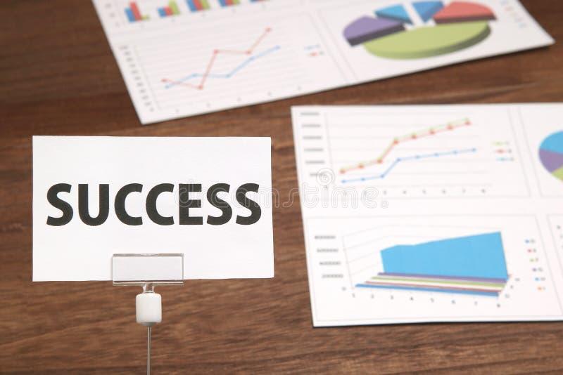 Palabra del éxito escrita en un trozo de papel delante de documentos de negocio imágenes de archivo libres de regalías