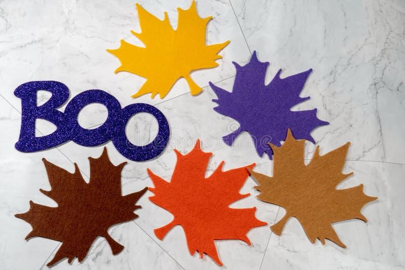 Palabra del abucheo para Halloween en las letras púrpuras relucientes, hojas de arce coloridas del fieltro foto de archivo