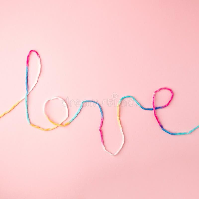 Palabra del amor escrita con las letras, concepto y el fondo de lana del hilo para el día de tarjeta del día de San Valentín, esp fotografía de archivo