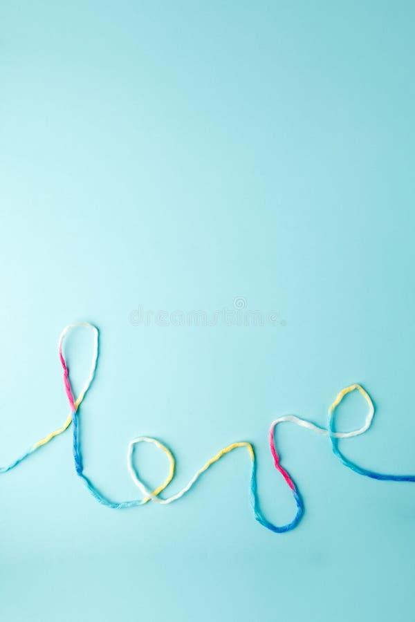 Palabra del amor escrita con las letras, concepto y el fondo de lana del hilo para el día de tarjeta del día de San Valentín, esp imagenes de archivo
