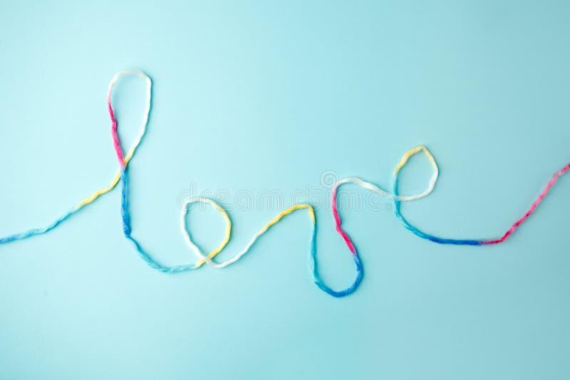 Palabra del amor escrita con las letras, concepto y el fondo de lana del hilo para el día de tarjeta del día de San Valentín, esp fotografía de archivo libre de regalías