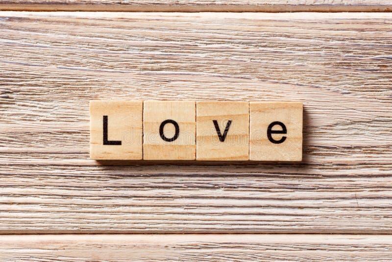 Palabra del amor escrita en el bloque de madera texto en la tabla, concepto del amor imagen de archivo