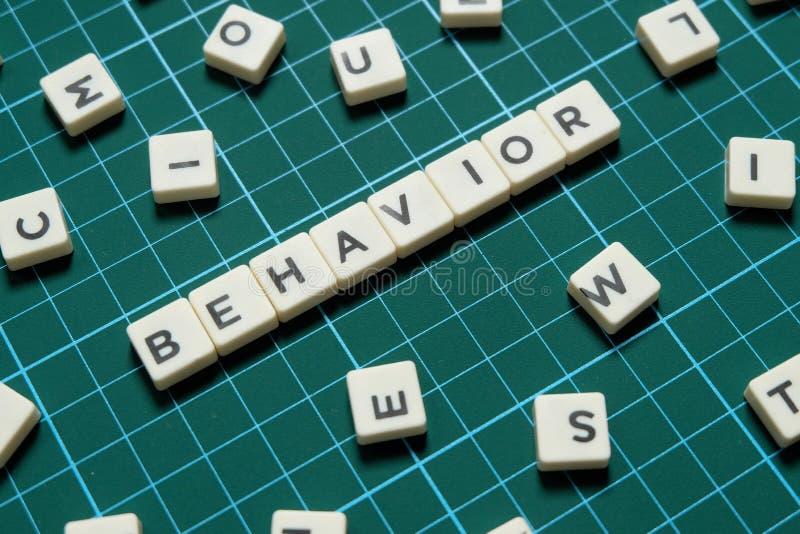 Palabra del comportamiento hecha de palabra cuadrada de la letra en fondo cuadrado verde de la estera foto de archivo libre de regalías