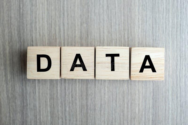 Palabra del negocio de los DATOS conceptual con el bloque de madera de los cubos en fondo de la tabla imagenes de archivo