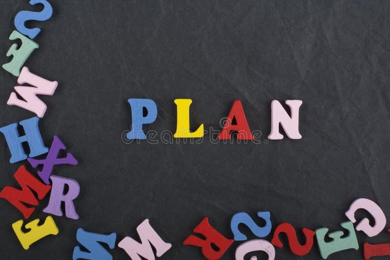 Palabra del PLAN en el fondo negro compuesto de letras de madera del ABC del bloque colorido del alfabeto, espacio del tablero de imagen de archivo libre de regalías