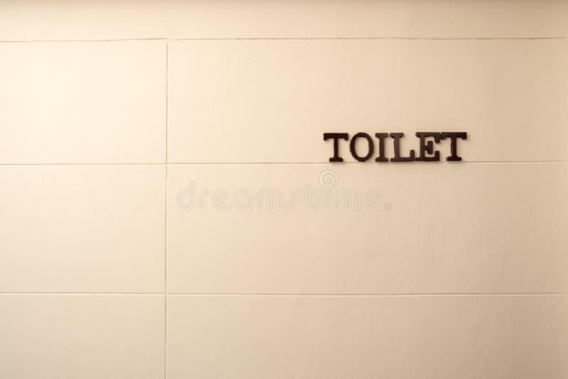 Palabra del retrete hecha del metal rústico que cuelga en la pared blanca imágenes de archivo libres de regalías