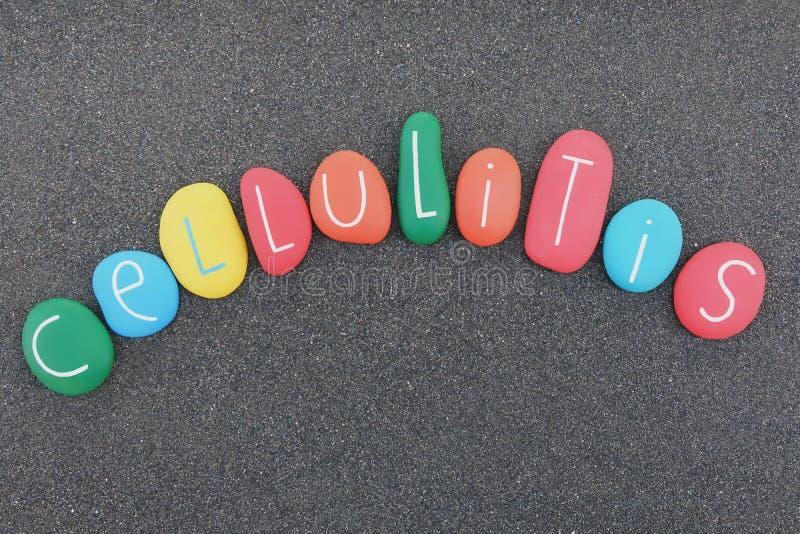 Palabra del texto de la celulitis con las piedras multicoloras del mar sobre la arena volcánica negra fotografía de archivo libre de regalías