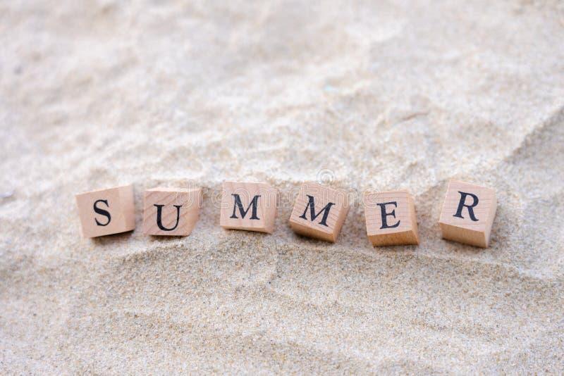 Palabra del verano escrita en el bloque de madera puesto en la playa de la arena Opini?n del mar durante d3ia con el fondo del ci fotos de archivo libres de regalías