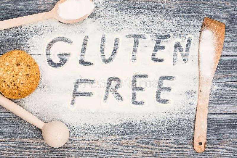 Palabra libre del gluten escrita en la harina y la tabla de madera imágenes de archivo libres de regalías