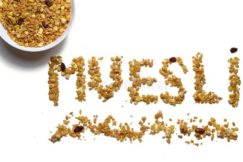 Palabra MUESLI con una placa del cereal en un fondo aislado blanco foto de archivo libre de regalías