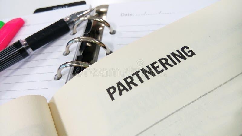 Palabra Partnering impresa en el libro blanco fotografía de archivo libre de regalías