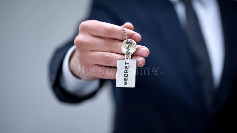 Palabra secreta en llavero en la mano del hombre de negocios, acceso a la información confidencial imagen de archivo libre de regalías