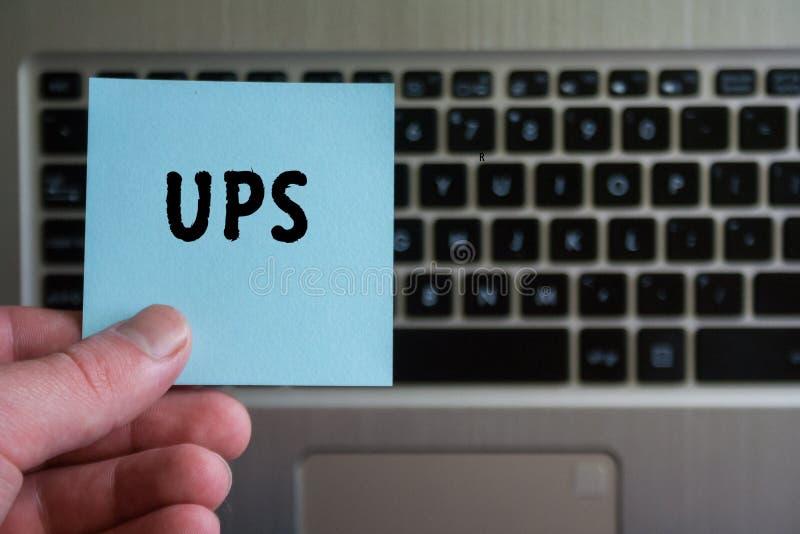 Palabra UPS en el control pegajoso de la nota a disposición del fondo del teclado foto de archivo libre de regalías