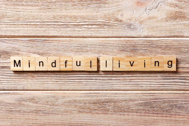 Palabra viva atenta escrita en el bloque de madera texto vivo atento en la tabla, concepto fotografía de archivo