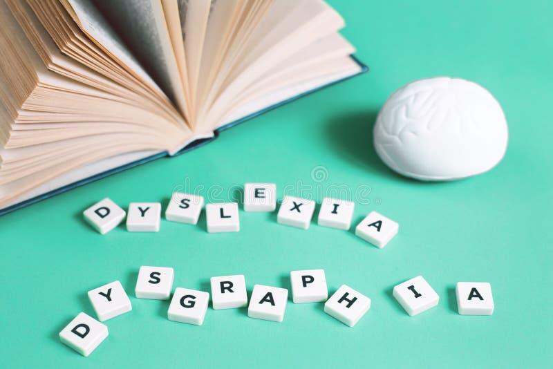 Palabras de la dislexia y de la lectura con un libro abierto imágenes de archivo libres de regalías