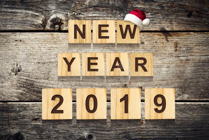 Palabras de la Feliz Año Nuevo 2019 compuestas de alfabeto en los cubos de madera Fondo de madera La Navidad, fondo del Año Nuevo imagen de archivo