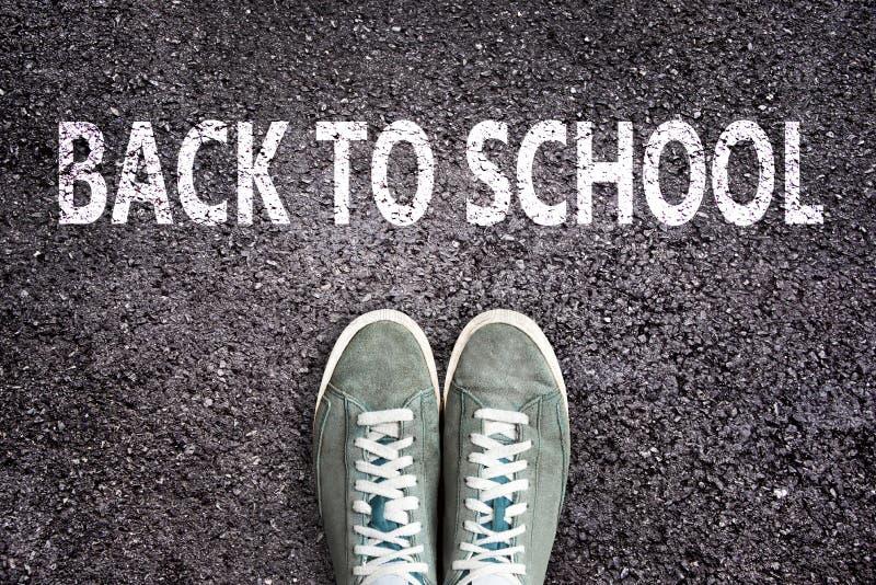 Palabras de nuevo a la escuela escrita en la carretera de asfalto con los zapatos de las zapatillas de deporte, a la High School  fotos de archivo