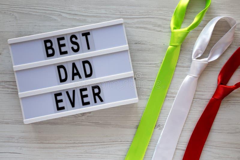 Palabras en tablero lmodern, lazos coloreados del 'mejor papá nunca 'sobre el fondo de madera blanco, visión superior Concepto de imagenes de archivo