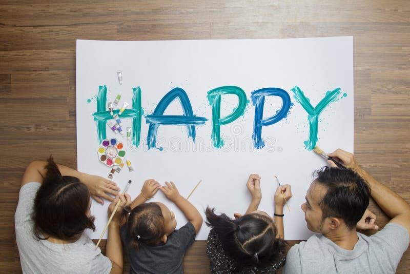 Palabras felices de mentira de la pintura de la familia en el papel en su sitio en casa fotografía de archivo libre de regalías