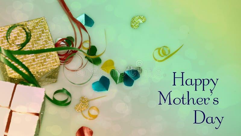 Palabras felices del día de madre con las pequeñas cajas en forma de corazón y de regalo coloridas como fondo imagenes de archivo