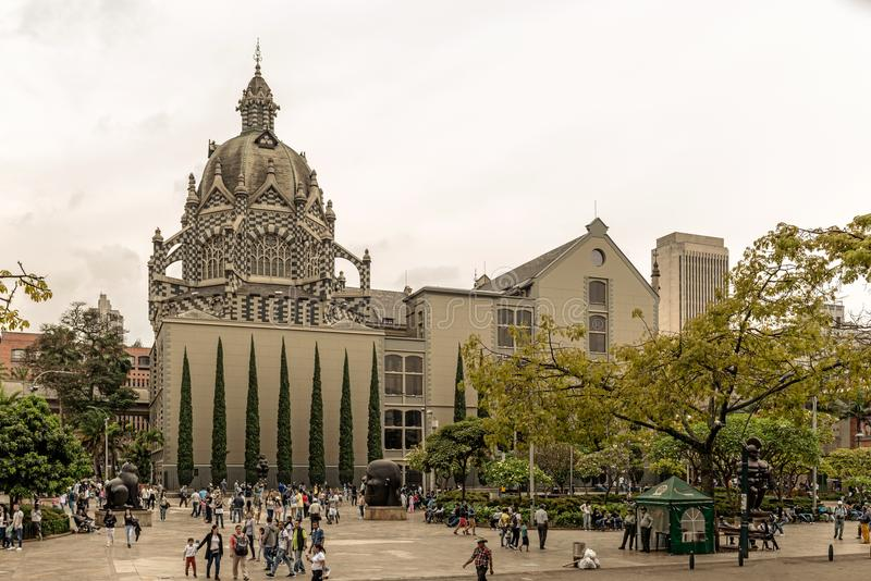 Palace of Culture Rafael Uribe Uribe and Coltejer Building symbols of the city. Medellin, Colombia - March 29, 2018: Tourists walking at Botero Plaza in Medellin royalty free stock image