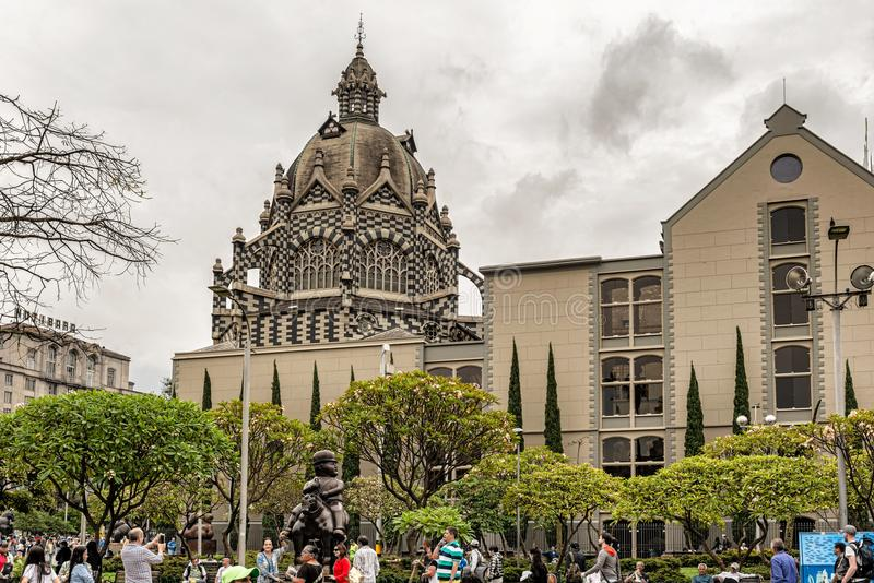 Palace of Culture Rafael Uribe Uribe and Coltejer Building symbols of the city. Medellin, Colombia - March 29, 2018: Tourists walking at Botero Plaza in Medellin royalty free stock photography