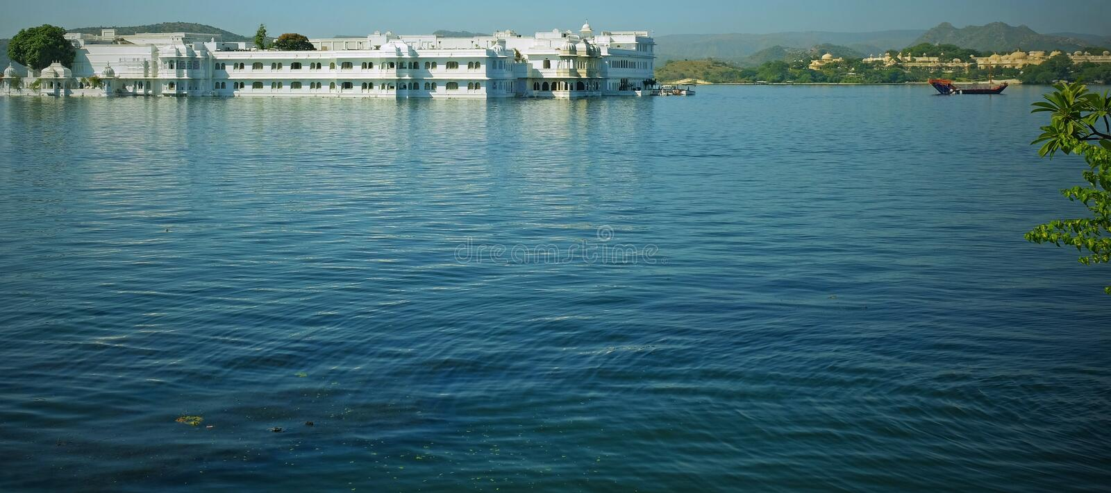 Palace on the lake. UDAIPUR, INDIA - NOVEMBER 10, 2016: View across Lake Pichola with the 18th century white marble palace, known as the Jag Niwas, and the royalty free stock photo