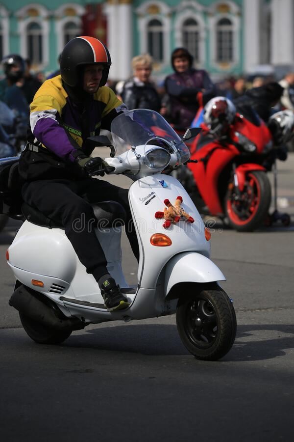 Palace Square. Young man rides on a white scooter Vespa, close-up royalty free stock photos