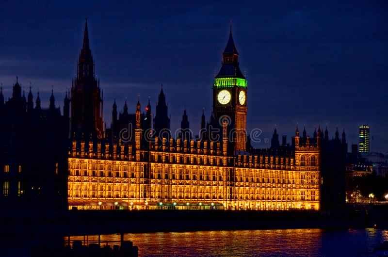 Palace of Westminster. Exterior of Palace of Westminster with Big Ben clock tower illuminated at night over Thames river, London, England royalty free stock photography