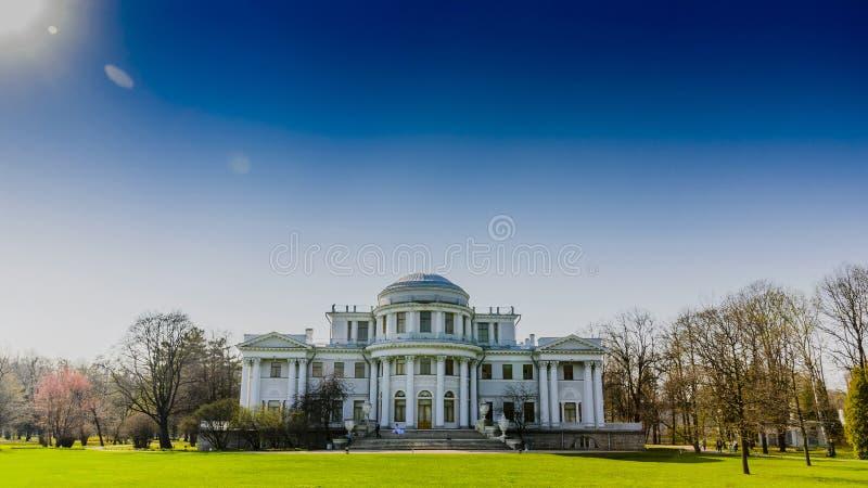 Palacio con el césped verde y el cielo azul imagenes de archivo
