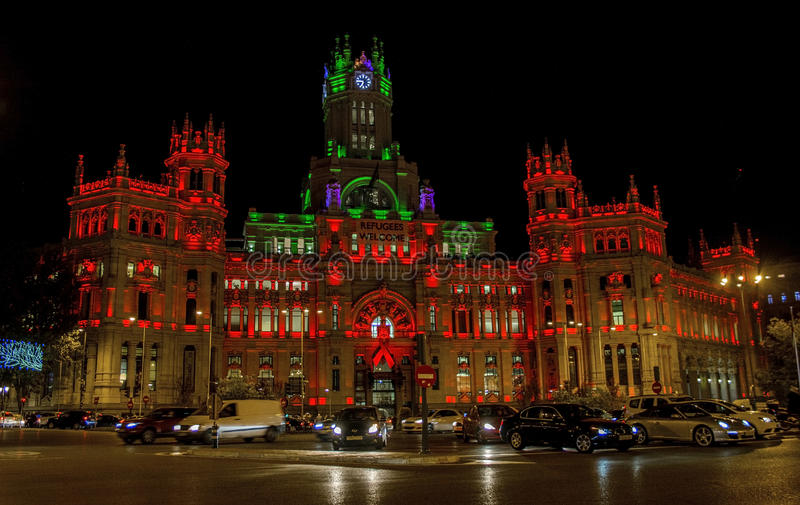 Palacio de Comunicaciones building at night with red lights and ribbon symbolizing AIDS international day. Madrid, Spain - December 1st, 2015 - Palacio de royalty free stock image