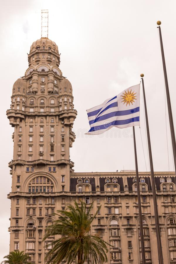 The Palacio Salvo and the Uruguayan flag, in the independence square of Montevido, the center of the capital of Uruguay, two. Emblems or icons of the country royalty free stock photos
