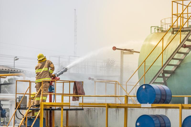Palacz trzyma pożarniczego węża elastycznego nozzle opryskiwania piany wody kontroli bój w żółtym pożarniczego wojownika mundurze zdjęcia stock