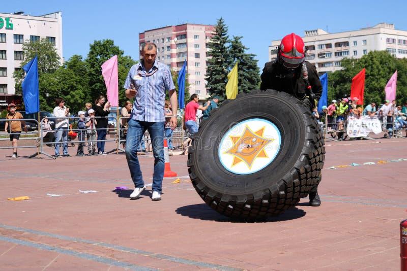 Palacz w fireproof kostiumu biega wielki gumowego i obraca toczy wewnątrz pożarniczego boju rywalizację, Białoruś, Minsk, 08 08 2 zdjęcie royalty free
