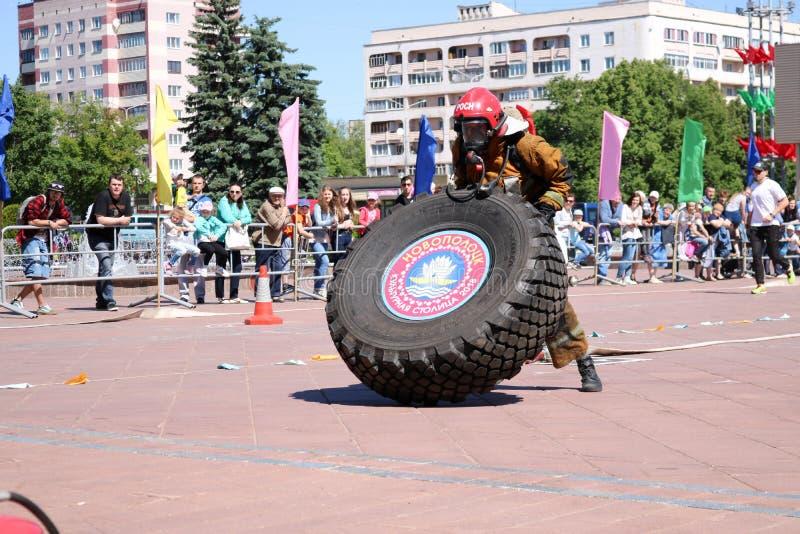 Palacz w fireproof kostiumu biega wielki gumowego i obraca toczy wewnątrz pożarniczego boju rywalizację, Białoruś, Minsk, 08 08 2 zdjęcia royalty free