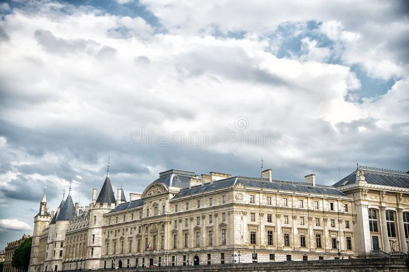 Palais de la Cite in Paris, France. Palace building with towers on cloudy sky. Monument of gothic architecture and design. Vacatio royalty free stock photography