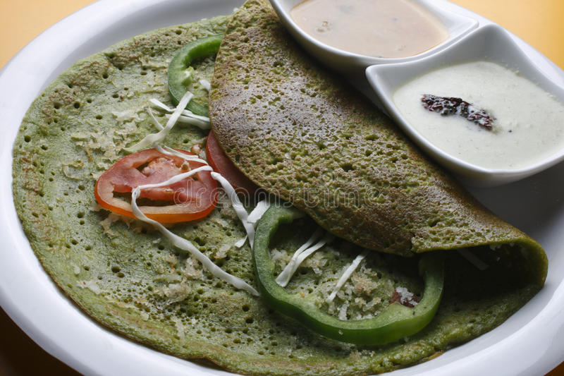Palak Dosa - A Crispy Spinach pancake. Palak pancake is made by Dosa flour,finely chopped palak,cumin seeds, pepper. This can be served with coconut chutney and royalty free stock photography