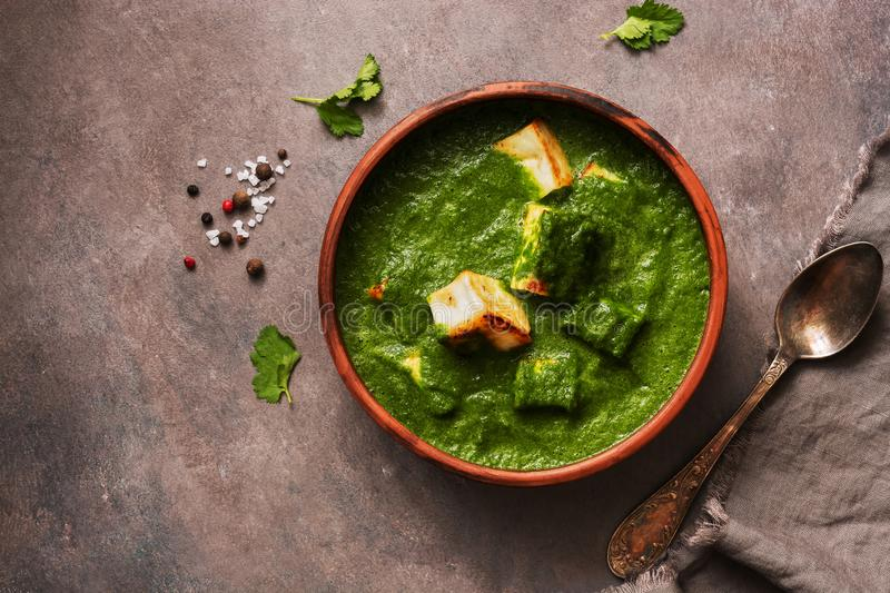 Palak paneer or Spinach and Cottage cheese curry on a dark background. Traditional Indian food. Top view, copy space royalty free stock photo