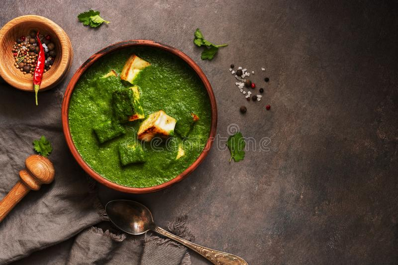 Palak paneer or Spinach and Cottage cheese curry,mortar with spices on a dark background. Traditional Indian dish. Top view, copy stock photography