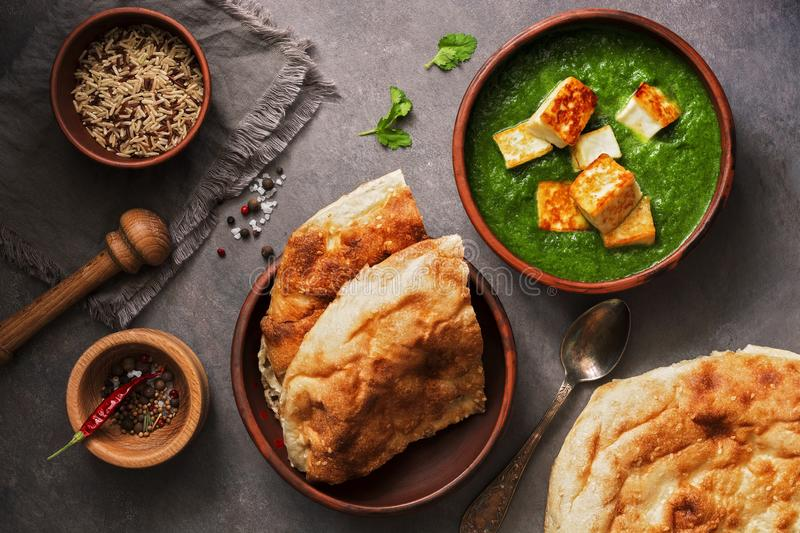 Palak paneer or Spinach and Cottage cheese curry,mortar with spices , naan, rice on a dark background. Traditional Indian food. stock photography
