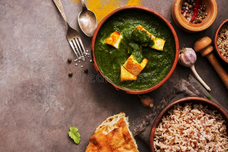 Palak paneer or Spinach and Cottage cheese curry,mortar with spices , naan, rice on a dark background. Traditional Indian food. stock photos