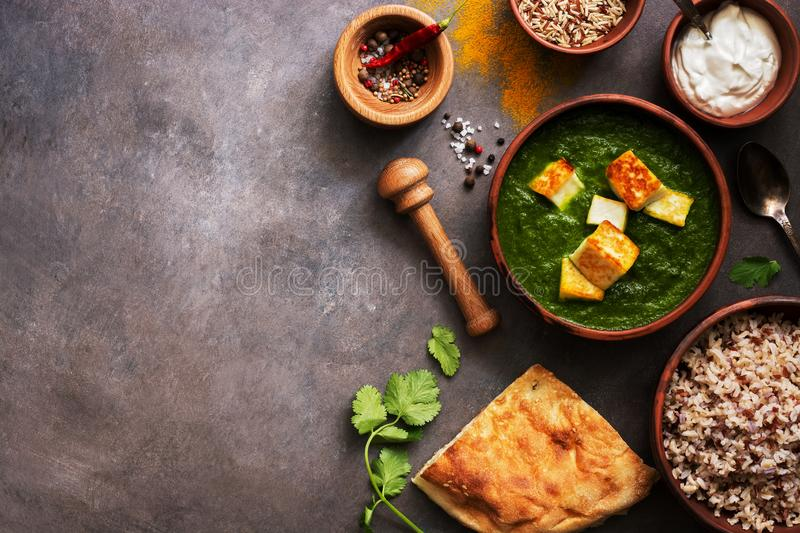 Palak paneer or Spinach and Cottage cheese curry,mortar with spices , naan, rice on a dark background. Traditional Indian food. Top view, copy space royalty free stock image