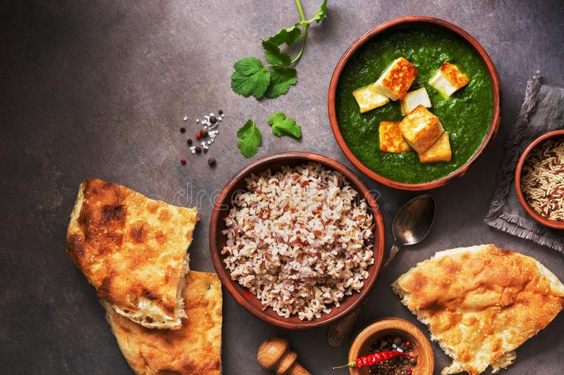 Palak paneer or Spinach and Cottage cheese curry, rice, spices , naan, on a dark background. Traditional Indian food. Top view, stock photos