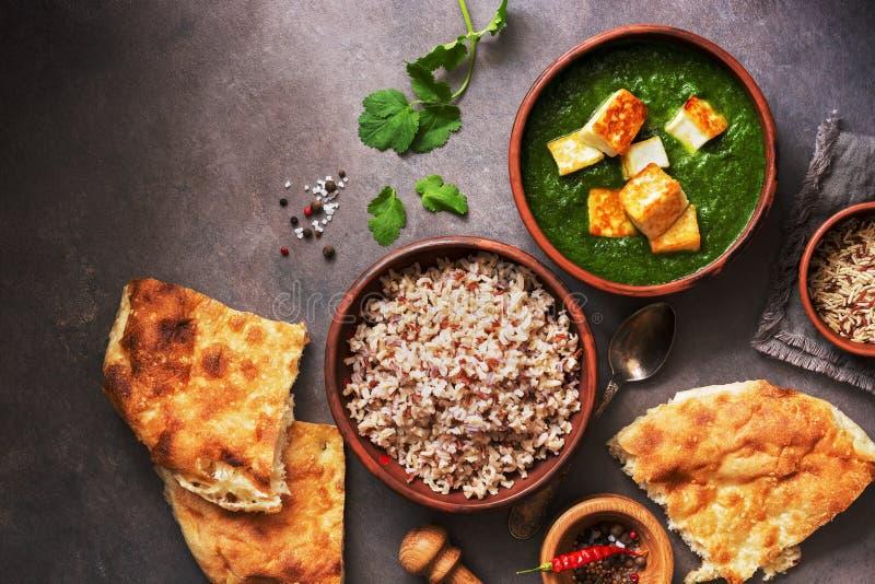 Palak paneer of Spinazie en kwarkkerrie, rijst, kruiden, naan, op een donkere achtergrond Traditioneel Indisch Voedsel hoogste me stock foto's