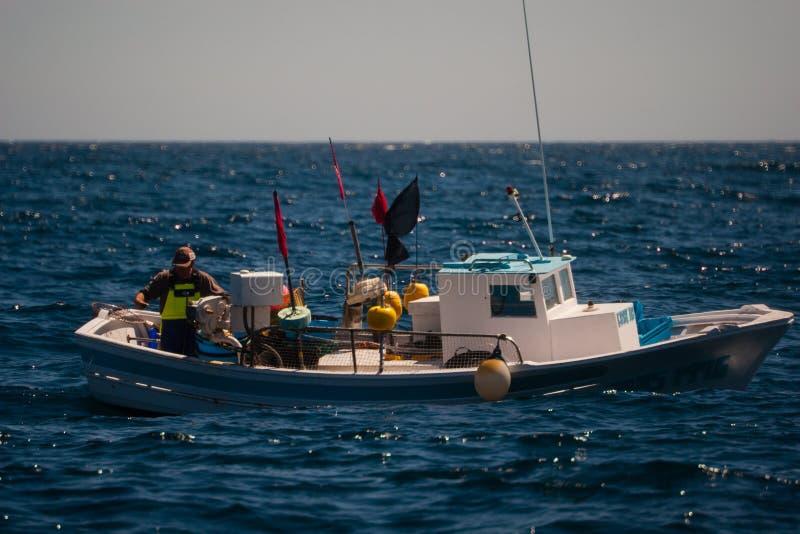 Palamos, Catalonië, kan 2016: Visser op een kleine boot stock fotografie